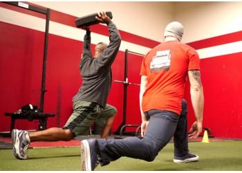 Инструктор кроссфит тренирует новичка